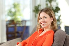Portrait of a happy woman sitting on a couch at home. Portrait of a happy woman in orange sitting on a couch in the living room at home Royalty Free Stock Photos