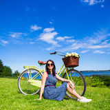 Portrait of happy woman sitting on the grass with vintage bicycl Stock Photography