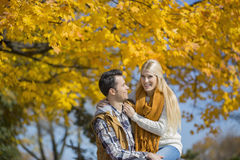 Portrait of happy woman sitting on man's lap in park during autumn Stock Image
