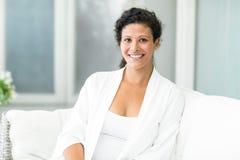 Portrait of happy woman sitting on sofa Stock Photos