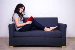 Portrait of happy woman sitting on sofa and reading book at home Stock Images