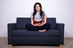 Portrait of happy woman sitting on sofa and reading book Stock Photo