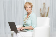 Portrait of a happy woman sitting using laptop Stock Photo