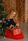 Portrait of a happy woman smiling and opening gift box. Happy New Year Royalty Free Stock Image