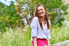 Portrait of a happy woman smiling outdoors. Portrait of smiling beautiful young woman close up, against background of summer green park Royalty Free Stock Photography
