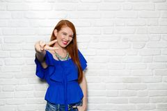 Facial Expressions Of Young Redhead Woman On Brick Wall. Portrait of happy woman smiling. Redhead girl looking at camera and doing peace sign with hand or V sign Stock Image