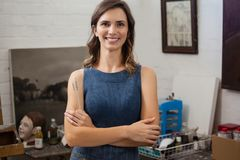 Portrait of happy woman standing with arms crossed. In drawing class stock image