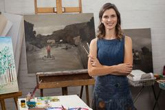 Portrait of happy woman standing with arms crossed. In drawing class royalty free stock images