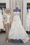 Portrait of a happy woman standing by elegant bridal dress in boutique Stock Photo
