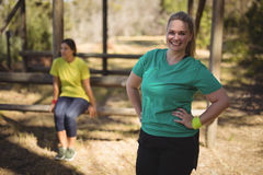 Portrait of happy woman standing with hands on hip during obstacle course Royalty Free Stock Images