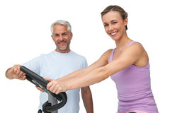 Portrait of a happy woman on stationary bike with trainer Stock Photography