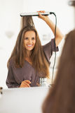 Portrait of happy woman straightening hair with straightener Royalty Free Stock Images