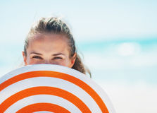 Portrait of happy woman in swimsuit hiding behind beach hat Stock Images