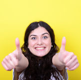 Portrait of happy woman with thumbs up against yellow background Royalty Free Stock Images