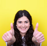 Portrait of happy woman with thumbs up against yellow background Royalty Free Stock Photos