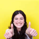 Portrait of happy woman with thumbs up against yellow background Royalty Free Stock Photo