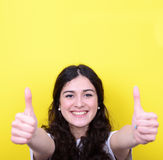 Portrait of happy woman with thumbs up against yellow background Royalty Free Stock Photography