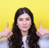 Portrait of happy woman with thumbs up against yellow background Royalty Free Stock Image