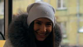 Portrait of happy woman during tram ride. Beautiful attractive girl walking on a winter city in Siberia stock video footage