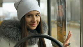 Portrait of happy woman during tram ride. Beautiful attractive girl walking on a winter city in Siberia stock footage