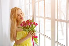 Portrait of happy woman with tulip bouquet. Portrait of happy woman with tulip bouquet, sunlight. copyspace Royalty Free Stock Image