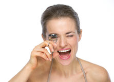 Portrait of happy woman using eyelash curler Royalty Free Stock Photography