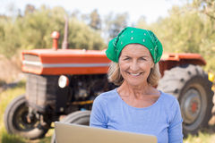 Portrait of happy woman using laptop in olive farm Stock Photos