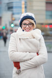 Portrait of happy woman in warm clothing standing arms crossed on city street Stock Images