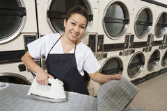 Portrait of a happy woman wearing apron ironing in front of washing machines Royalty Free Stock Photo