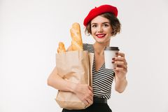Portrait of a happy woman wearing beret holding paper bag. With long loaf and cup of coffee isolated over white background Royalty Free Stock Images