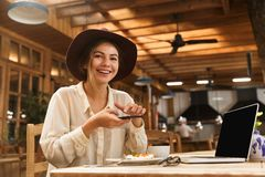 Portrait of happy woman wearing hat photographing food on cell phone stock photography