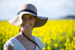 Portrait of happy woman wearing hat and standing in mustard field. On a sunny day Stock Photography