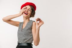 Portrait of a happy woman wearing red beret. Holding cookie and laughing isolated over white background Royalty Free Stock Photography