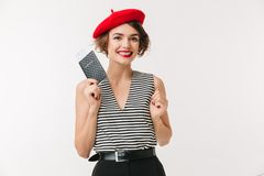 Portrait of a happy woman wearing red beret. Holding passport isolated over white background Stock Images
