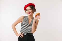 Portrait of a happy woman wearing red beret. Holding croissant isolated over white background Stock Photography