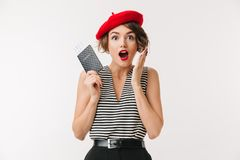 Portrait of a happy woman wearing red beret. Holding passport and celebrating isolated over white background Stock Images
