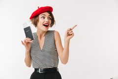 Portrait of a happy woman wearing red beret. Holding passport and pointing finger away isolated over white background Stock Image