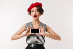 Portrait of a happy woman wearing red beret. Showing blank screen mobile phone isolated over white background Royalty Free Stock Photos