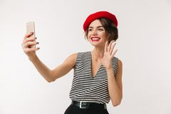 Portrait of a happy woman wearing red beret. Waving to camera isolated over white background Royalty Free Stock Photography