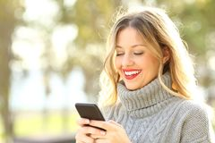 Happy woman reading text on phone in winter stock photography