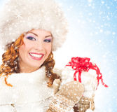 Portrait of a happy woman in a winter hat holding a present Royalty Free Stock Photography