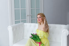 Portrait of happy woman in yellow dress with tulip bouquet on the couch. Stock Image