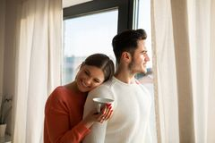 Happy woman with cup of coffee cuddling to her boyfriend stock photo