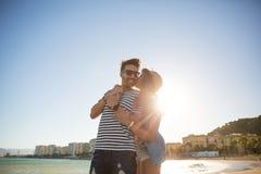 Happy woman embracing her boyfriend at seaside kissing him. Portrait of happy women embracing her boyfriend at seaside kissing him Stock Image