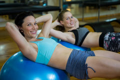 Portrait of happy women exercising on fitness ball Royalty Free Stock Photography