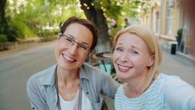 Portrait of happy women friends taking selfie in outdoor cafe posing having fun. Slow motion portrait of happy mature women friends taking selfie in outdoor cafe stock footage