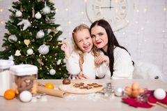 Happy woman and her cute daughter cooking Christmas cookies in k stock photos