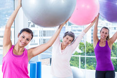 Portrait of happy women holding exercise balls with arms raised Stock Photo