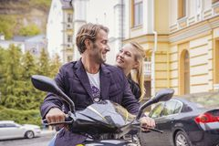Portrait of happy woman leaning on man while sitting on scooter Royalty Free Stock Images