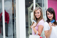 Portrait of happy women showing their credit cards in mall Royalty Free Stock Images